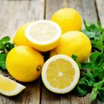 lemons and mint on a dark wood background. tinting. selective focus