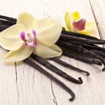 Vanilla sticks with a flower on a white wooden table.